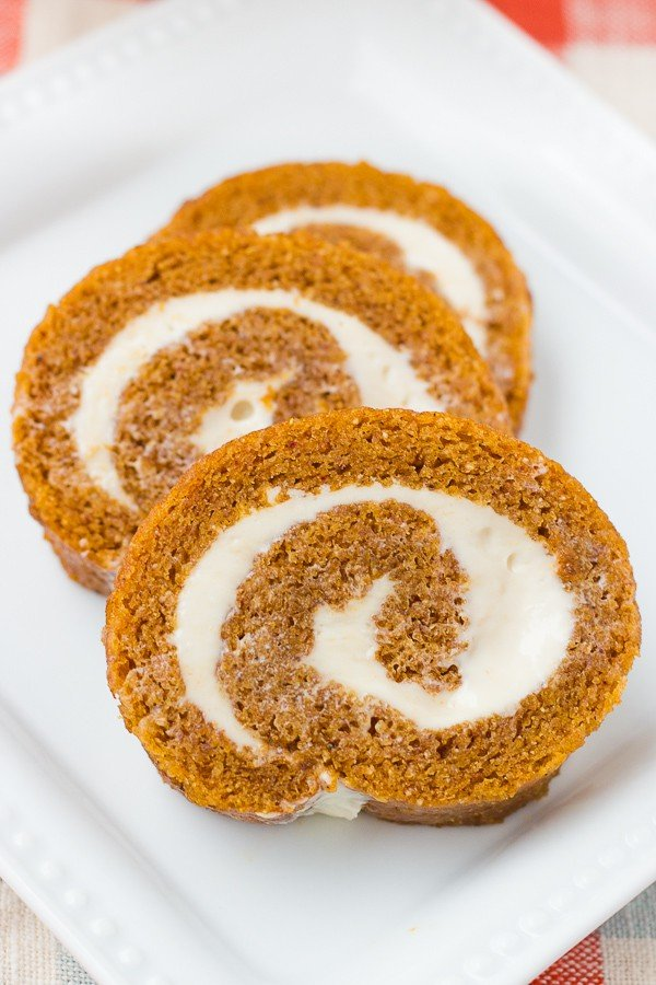 close up shot of sliced pumpkin roll on white plate