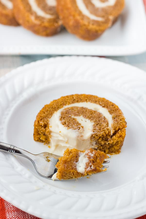 sliced pumpkin roll on white plate with fork
