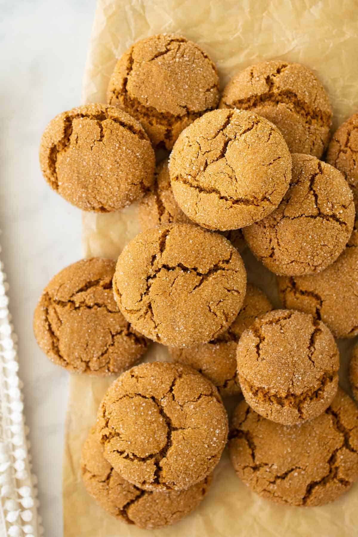 pile of molasses cookies stacked on brown parchment paper