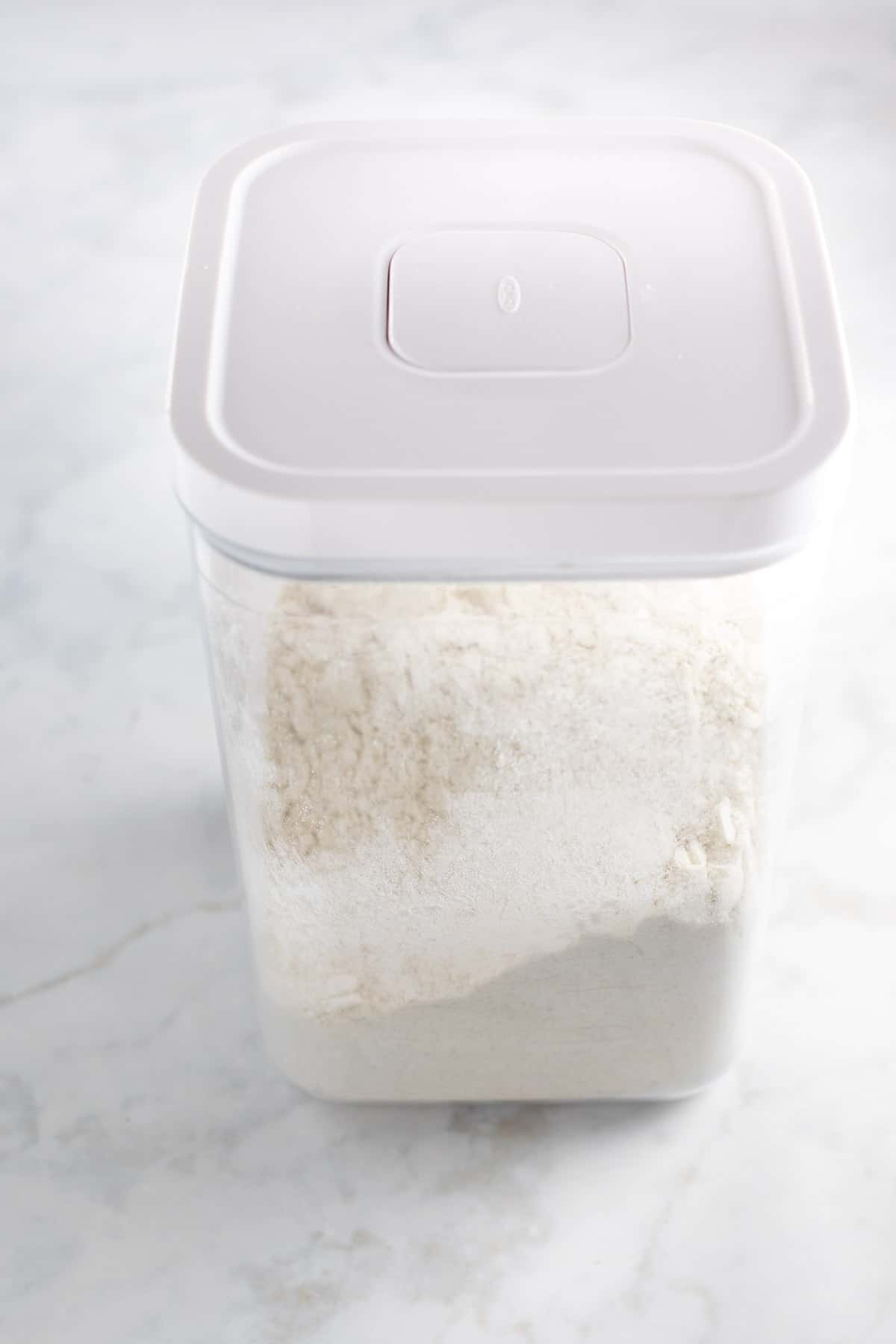 tall plastic tupperware container full of gluten-free flour