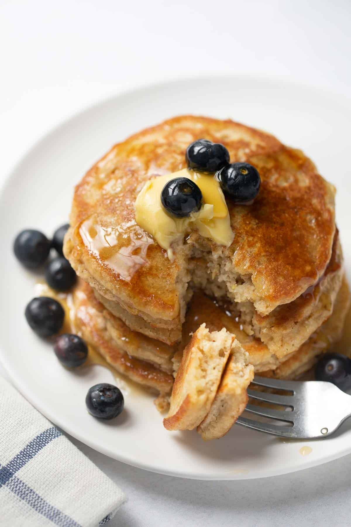 stalk of gluten-free pancakes on white plate with blueberries, syrup and fork with bite