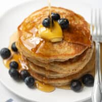 stack of gluten free pancakes with maple syrup and blueberries on white plate