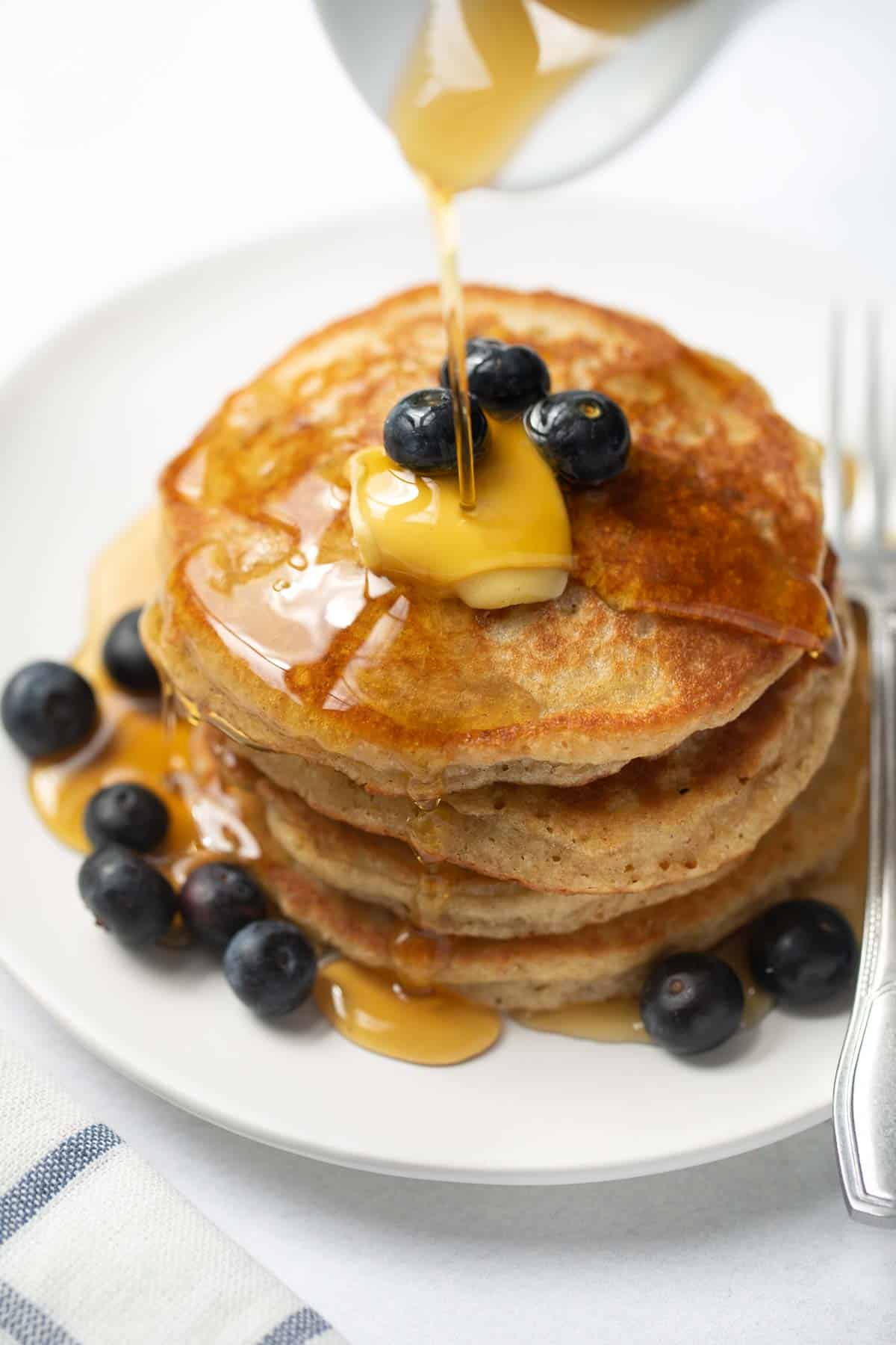 stack of gluten-free pancakes on white plate with syrup and blueberries