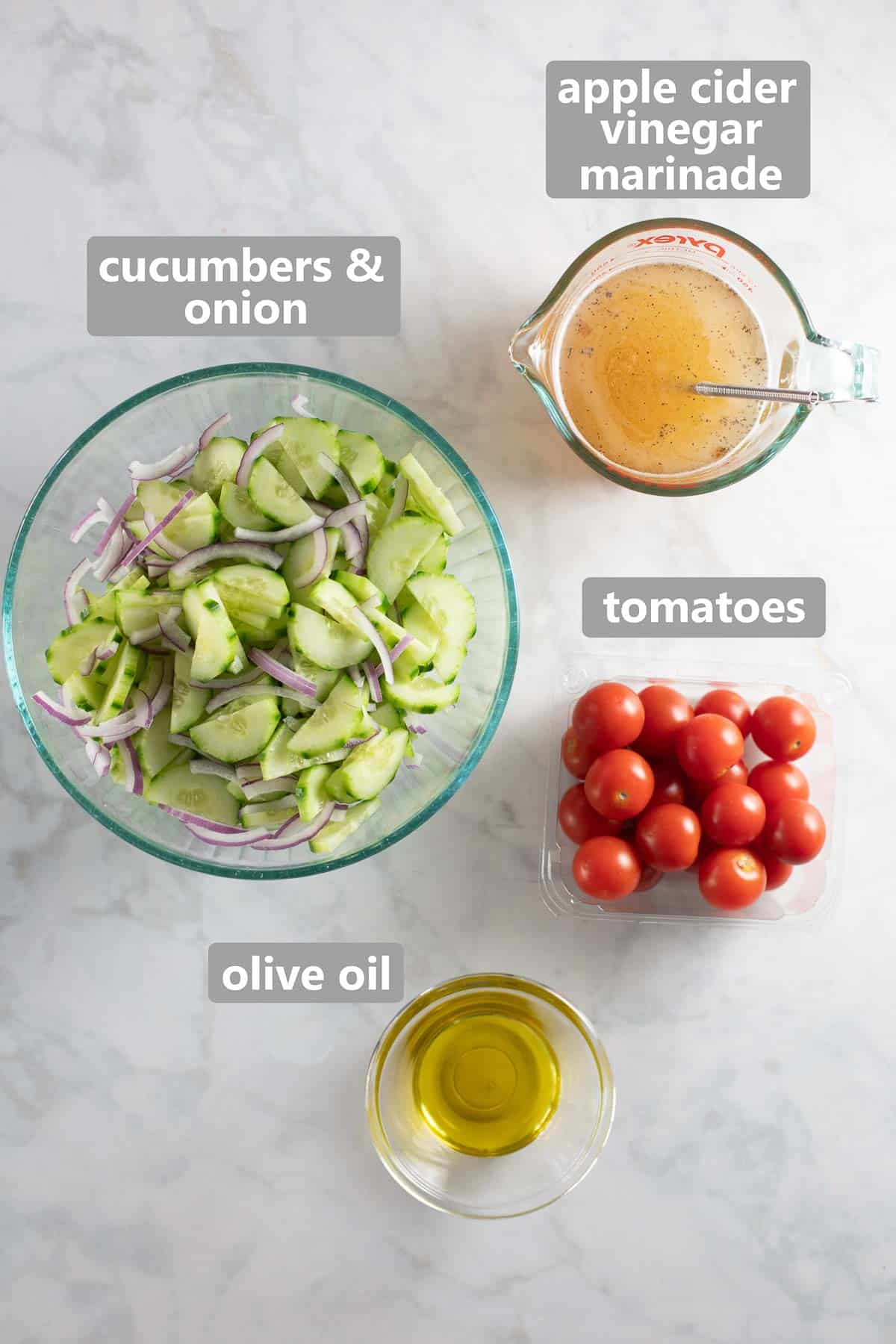 overhead photo of ingredients in clear glass bowls to make cucumber onion tomato salad and apple cider vinegar marinade