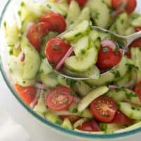 cucumber tomato salad in glass bowl with serving spoon