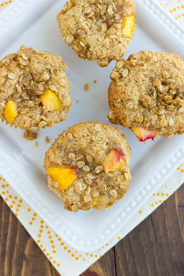 overhead shot of gluten free peach muffins on white plate