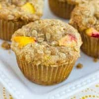 close up shot of peach muffin on white plate