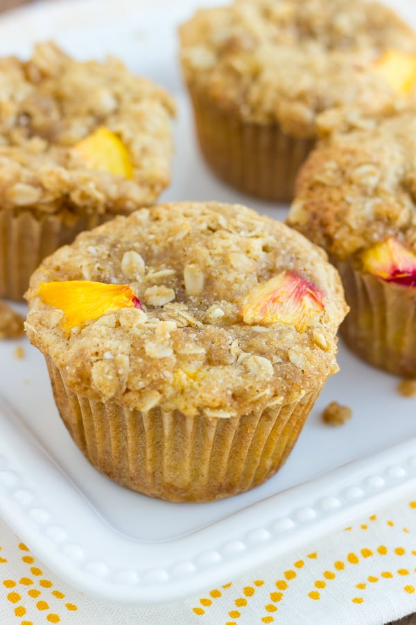 peach muffins on white plate with white and yellow cloth