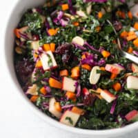 close up shot of kale salad in white bowl with serving spoon
