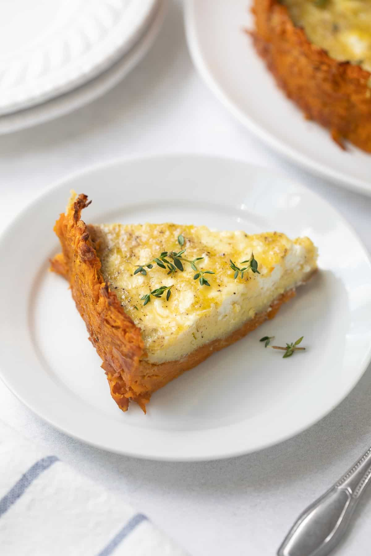 slice of goat cheese and leek quiche with sweet potato crust on a white plate