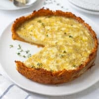 baked sweet potato crust quiche on a plate with a slice on a separate plate with fork