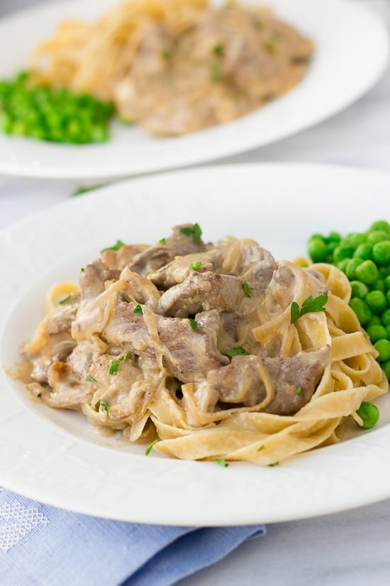 beef stroganoff on white plate topped with parsley