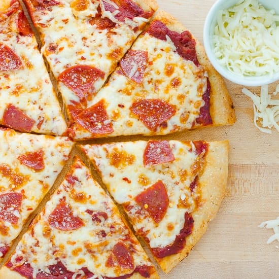 sliced pepperoni pizza on wooden cutting board
