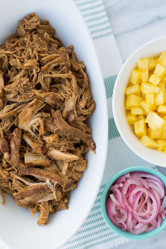 overhead shot of meat in bowl with pineapple and pickled onions