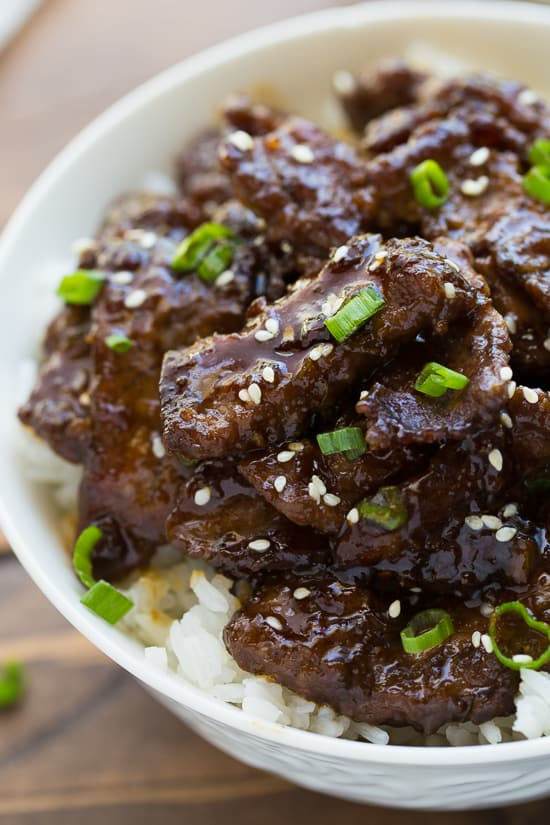 close up image of teriyaki beef garnished with scallions and sesame seeds