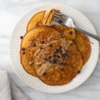 overhead shot of pumpkin pancakes on white plate topped with peanut butter and maple syrup