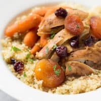 moroccan chicken over quinoa in white bowl