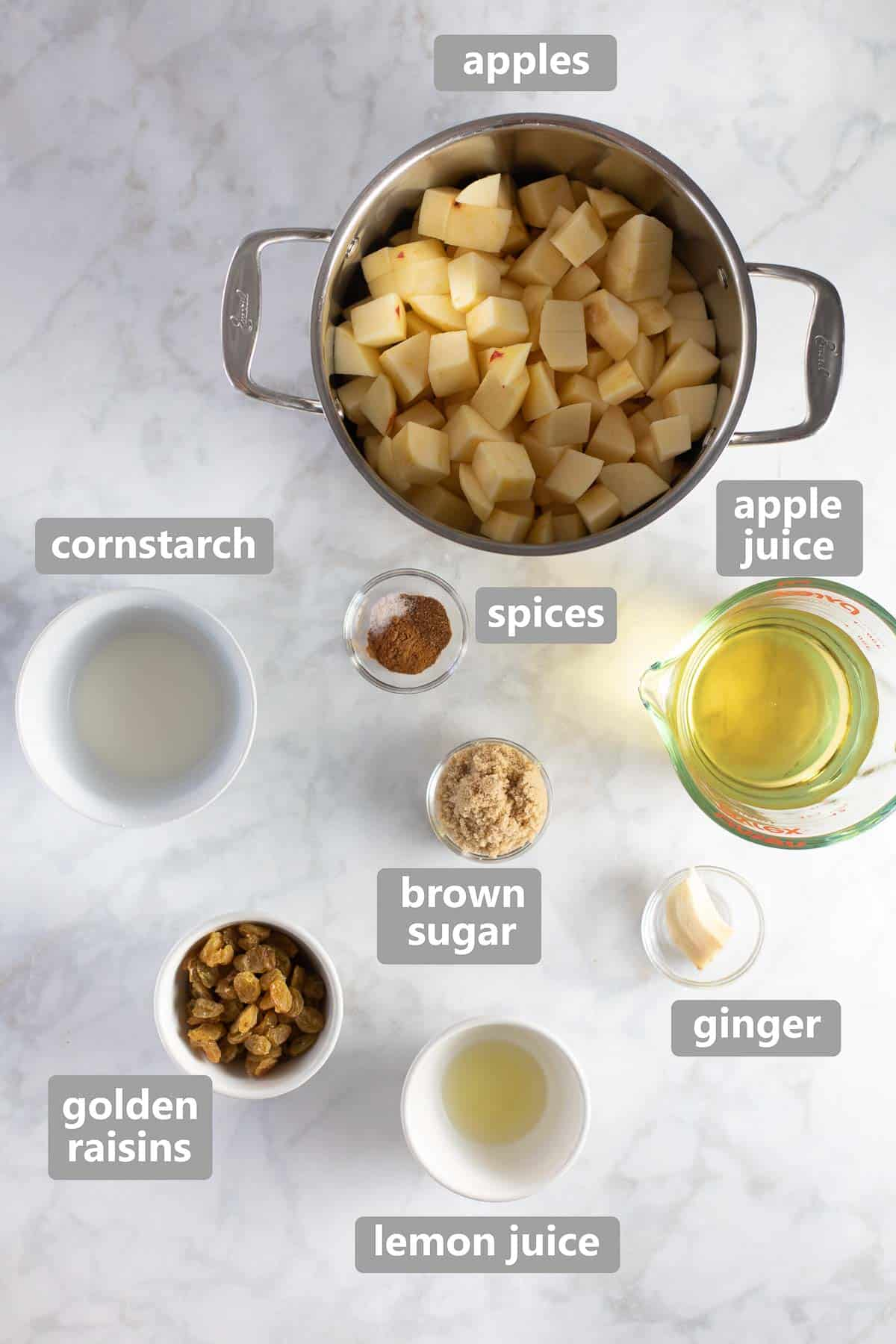 ingredients to make homemade applesauce on white marble background