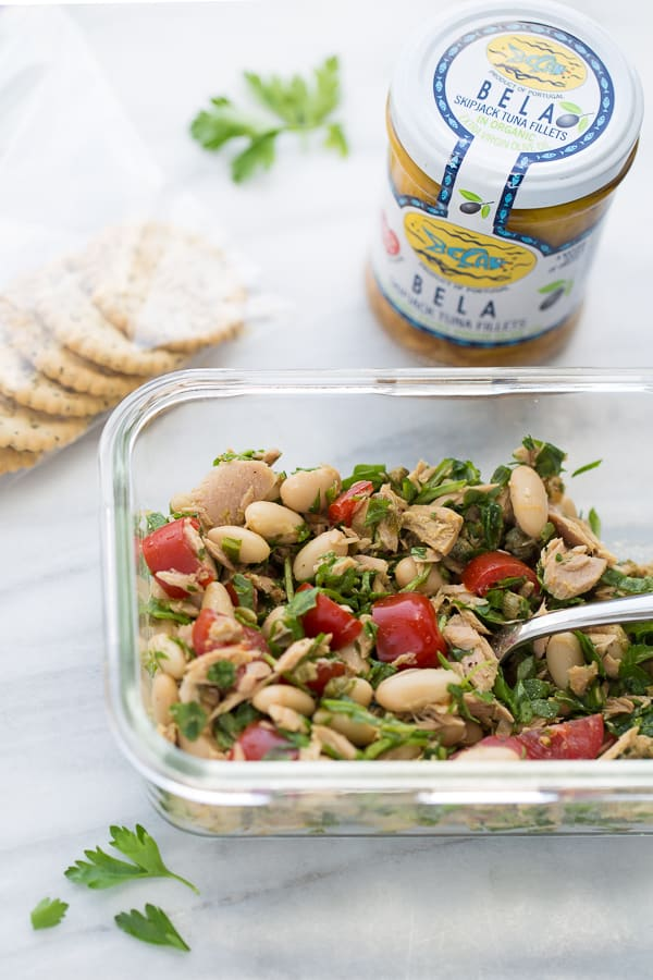 tuna salad in glass tupperware container topped with parsley and tuna in background