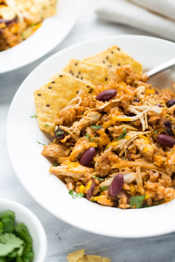 close up shot of chicken and rice in white bowl topped with tortilla chips and cheese