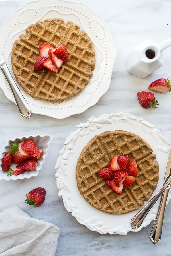 overhead shot of buckwheat waffles on white plates with strawberries