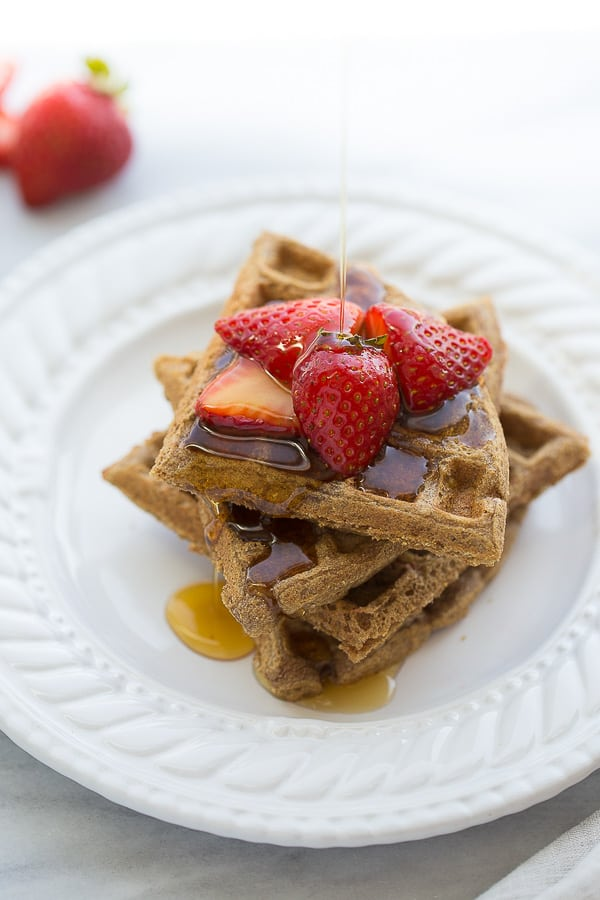 buckwheat waffles on white plate with strawberries and syrup