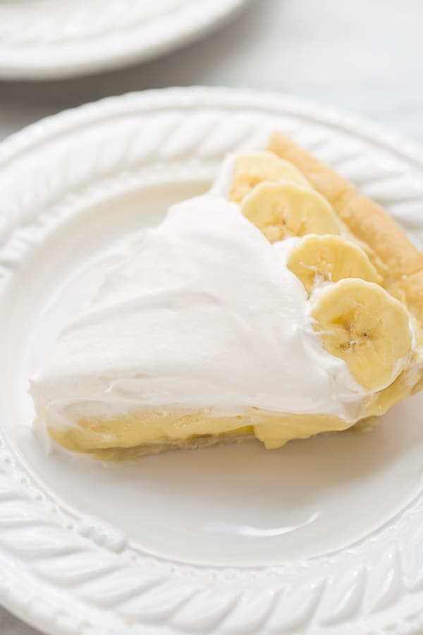 close up shot of sliced banana cream pie on white plate