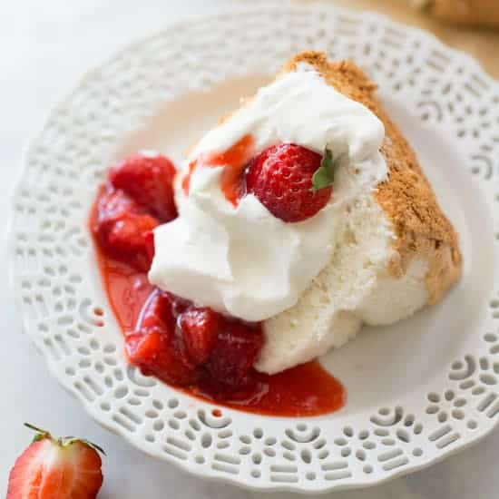 slice of gluten-free angel food cake on white plate with strawberries