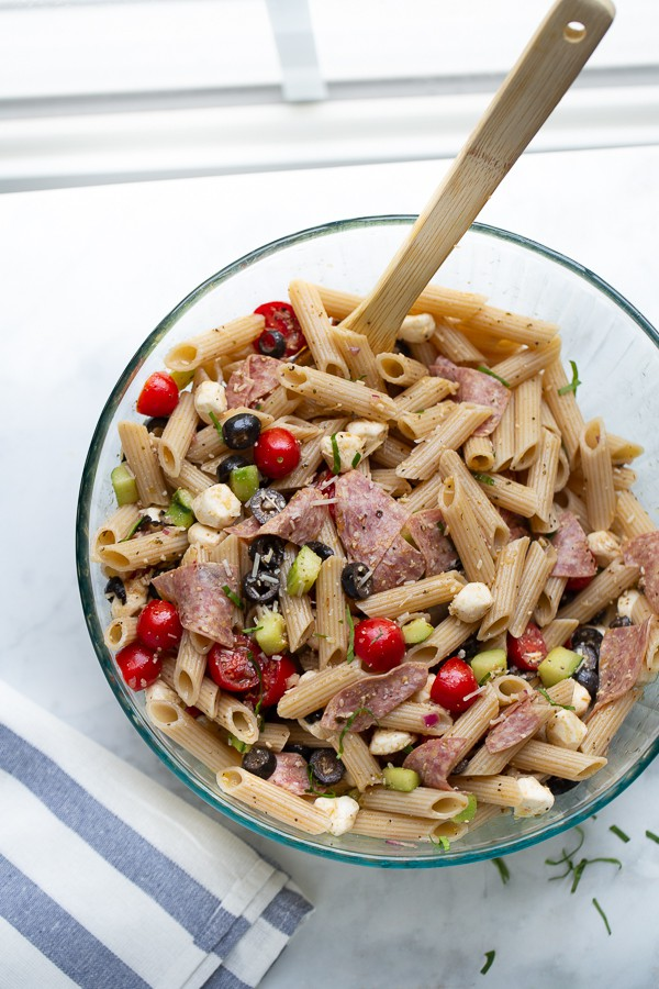 overhead shot of pasta salad in bowl with wooden spoon