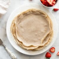 overhead shot of buckwheat crepes on white plate with strawberries
