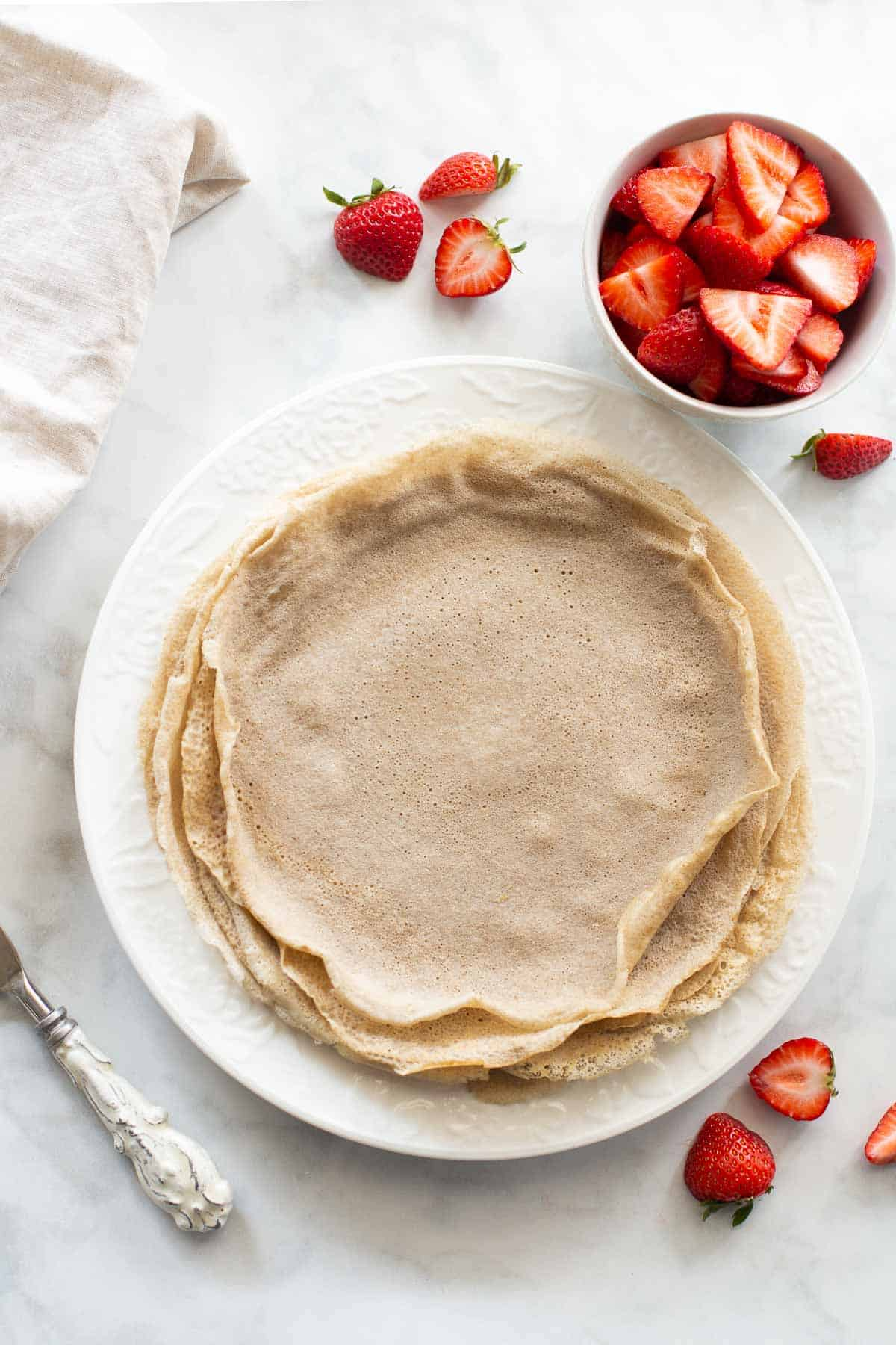 overhead of shot of buckwheat crepes on a white plate with strawberries