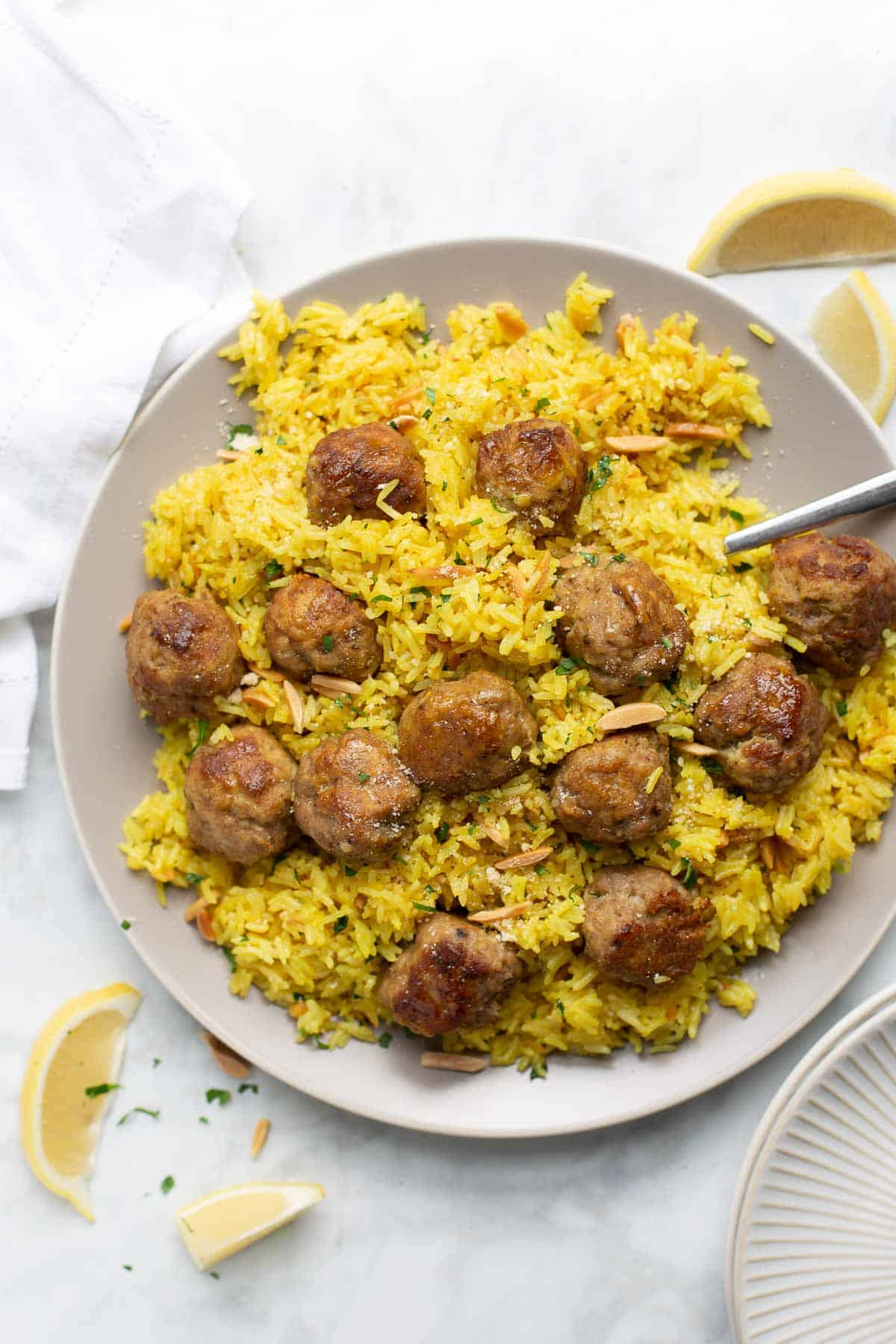 overhead shot of turkey meatballs and yellow rice on gray plate with white background