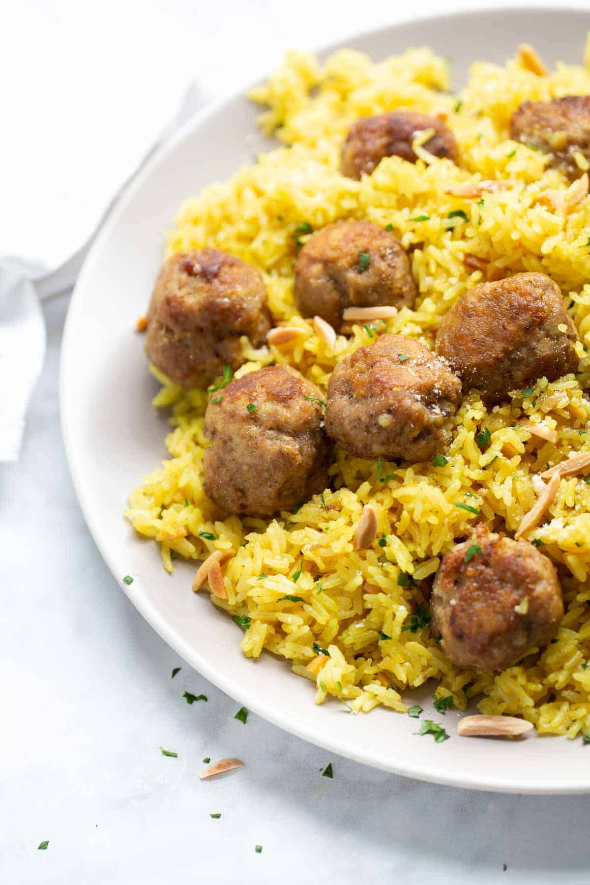 close up shot of turkey meatballs and rice on gray plate and marble background