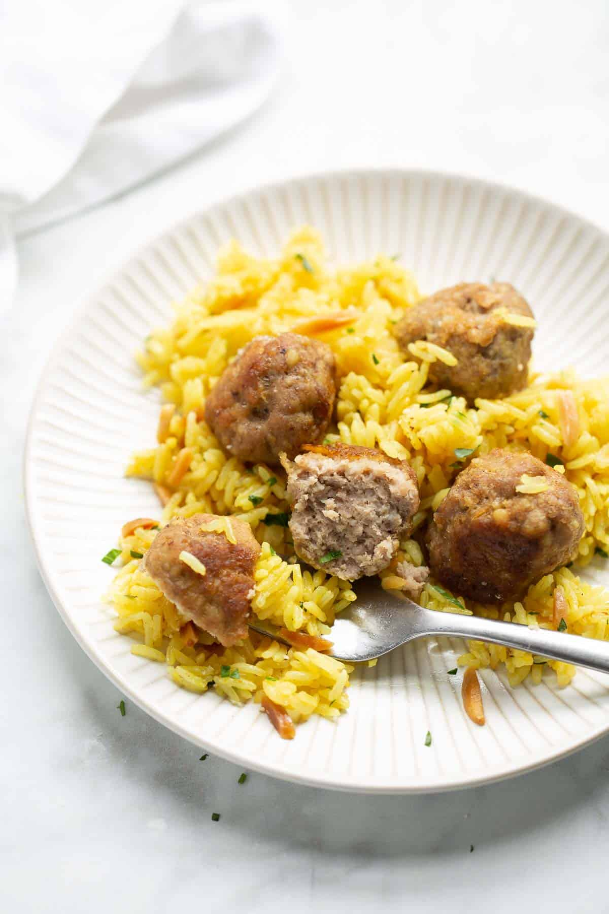 turkey meatball with bite on fork and yellow rice on white plate