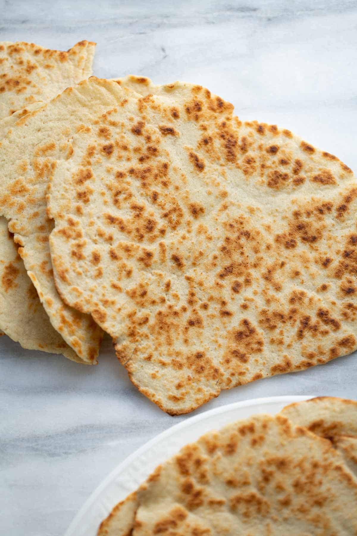 gluten-free flatbread stacked on white marble background