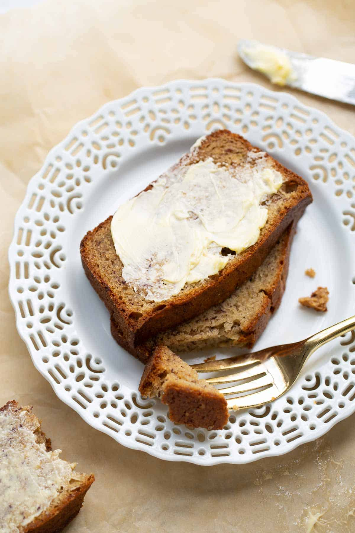 buttered banana bread on plate with fork taking a bite