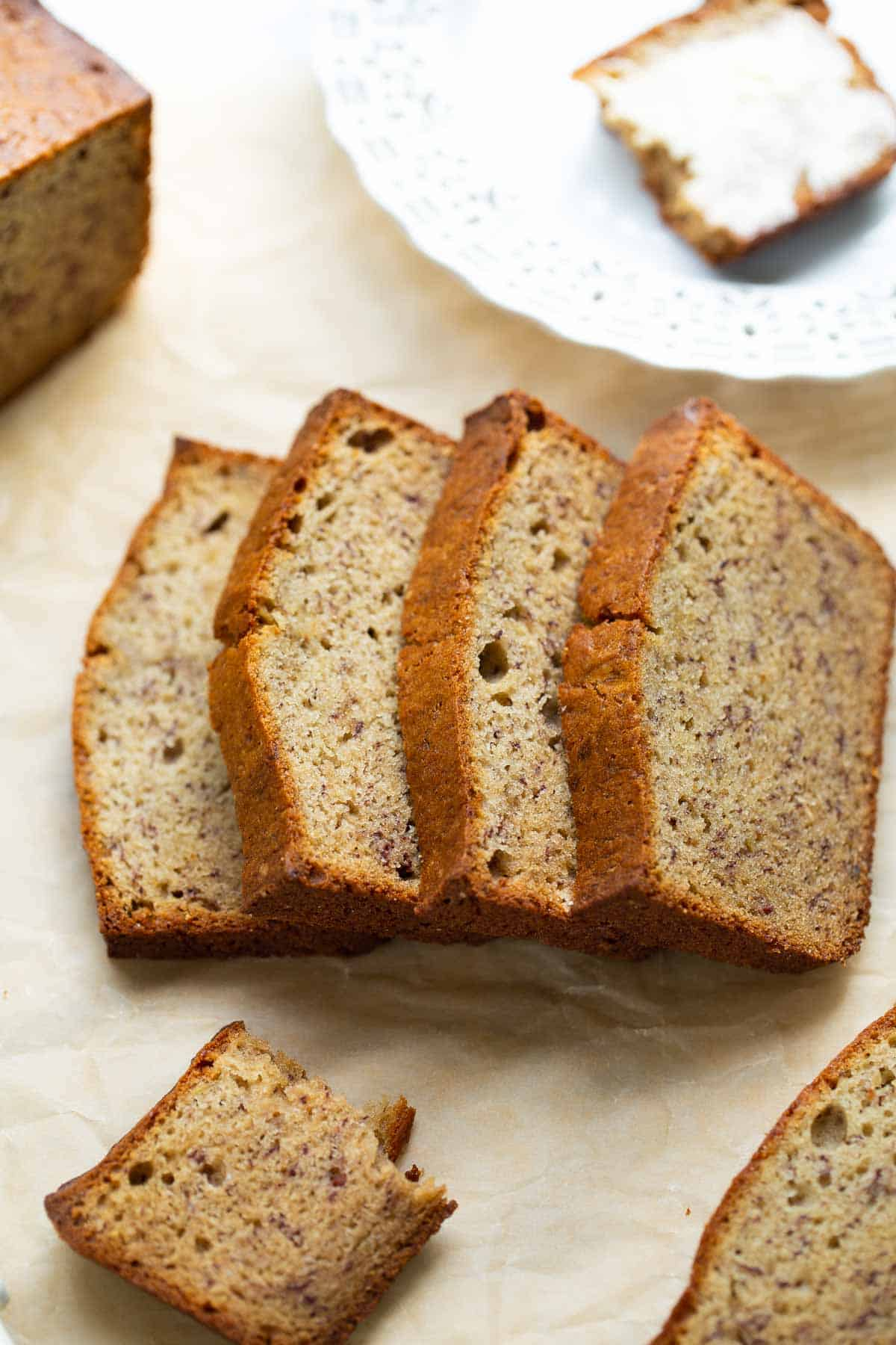 slices of banana bread on parchment paper with plate with buttered banana bread in background