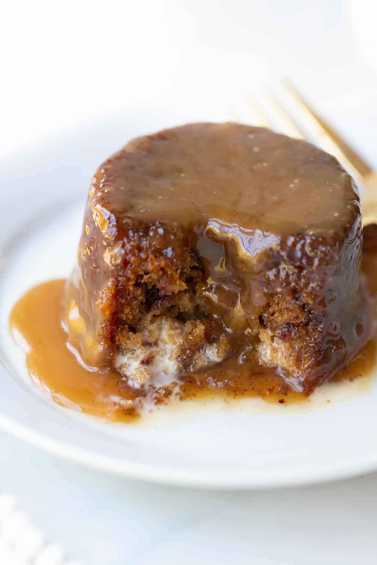 close up shot of sticky toffee pudding covered in sauce on white plate