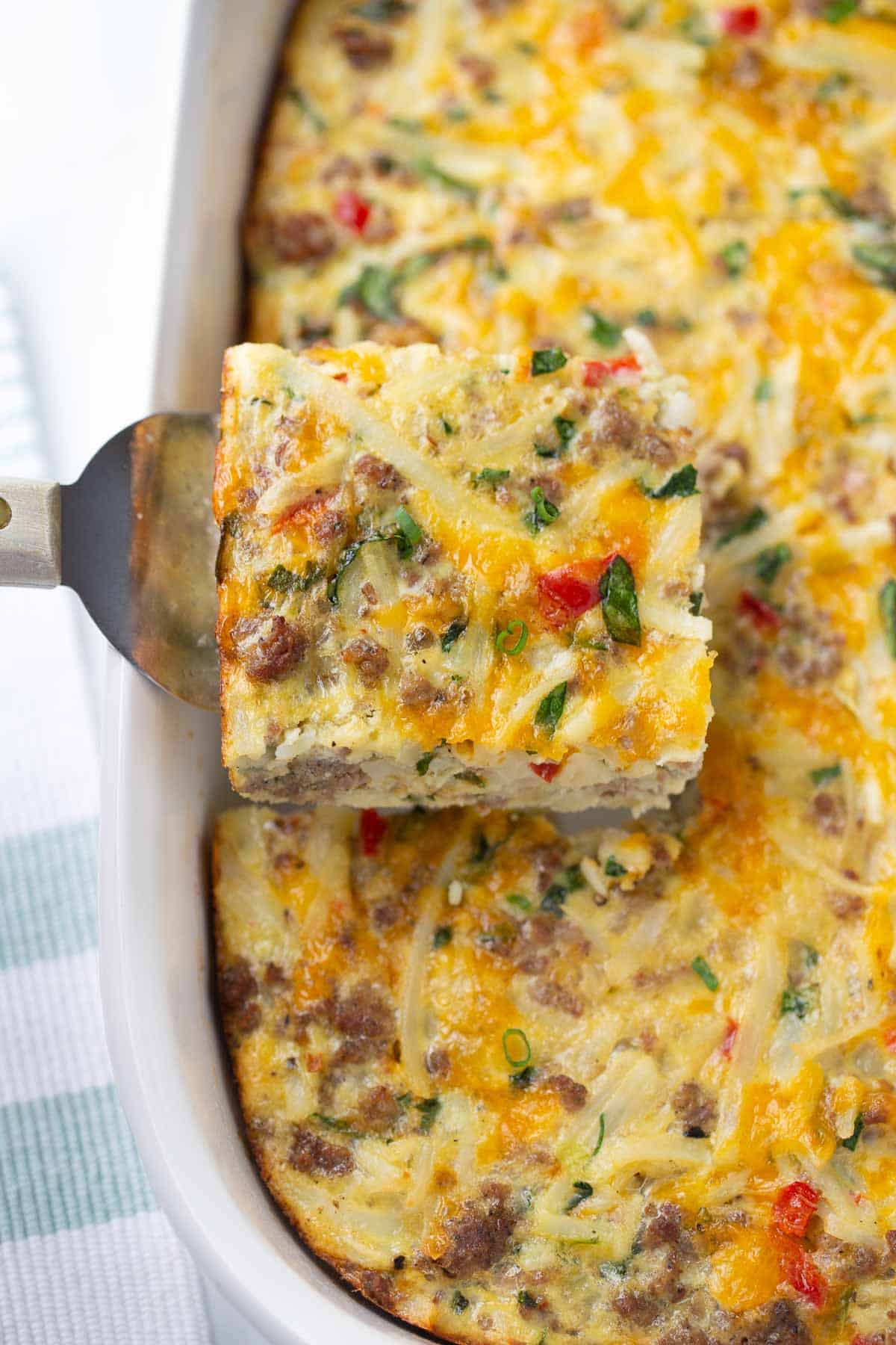breakfast casserole being served from white casserole dish with spatula