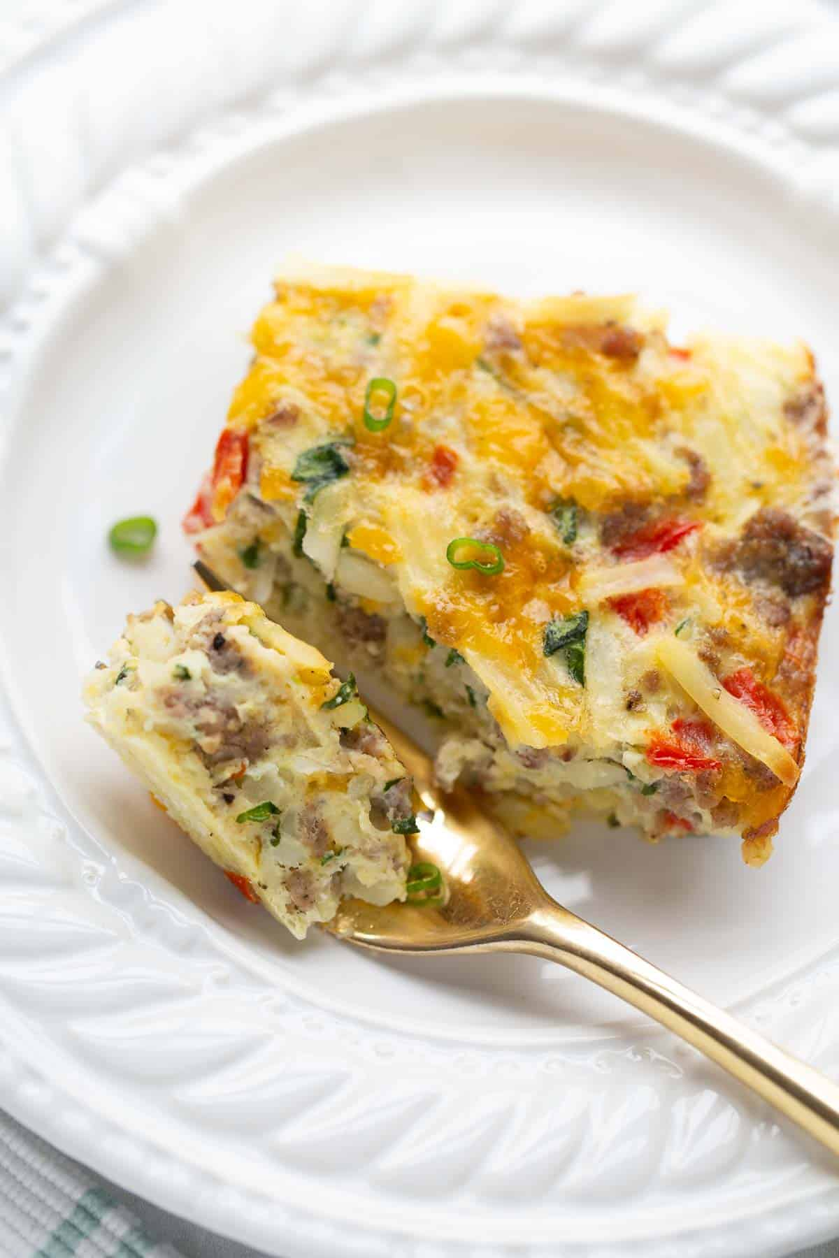 breakfast casserole on white plate with gold fork