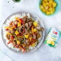 pork pineapple stir fry over rice on gray plate with can of Dole pineapple