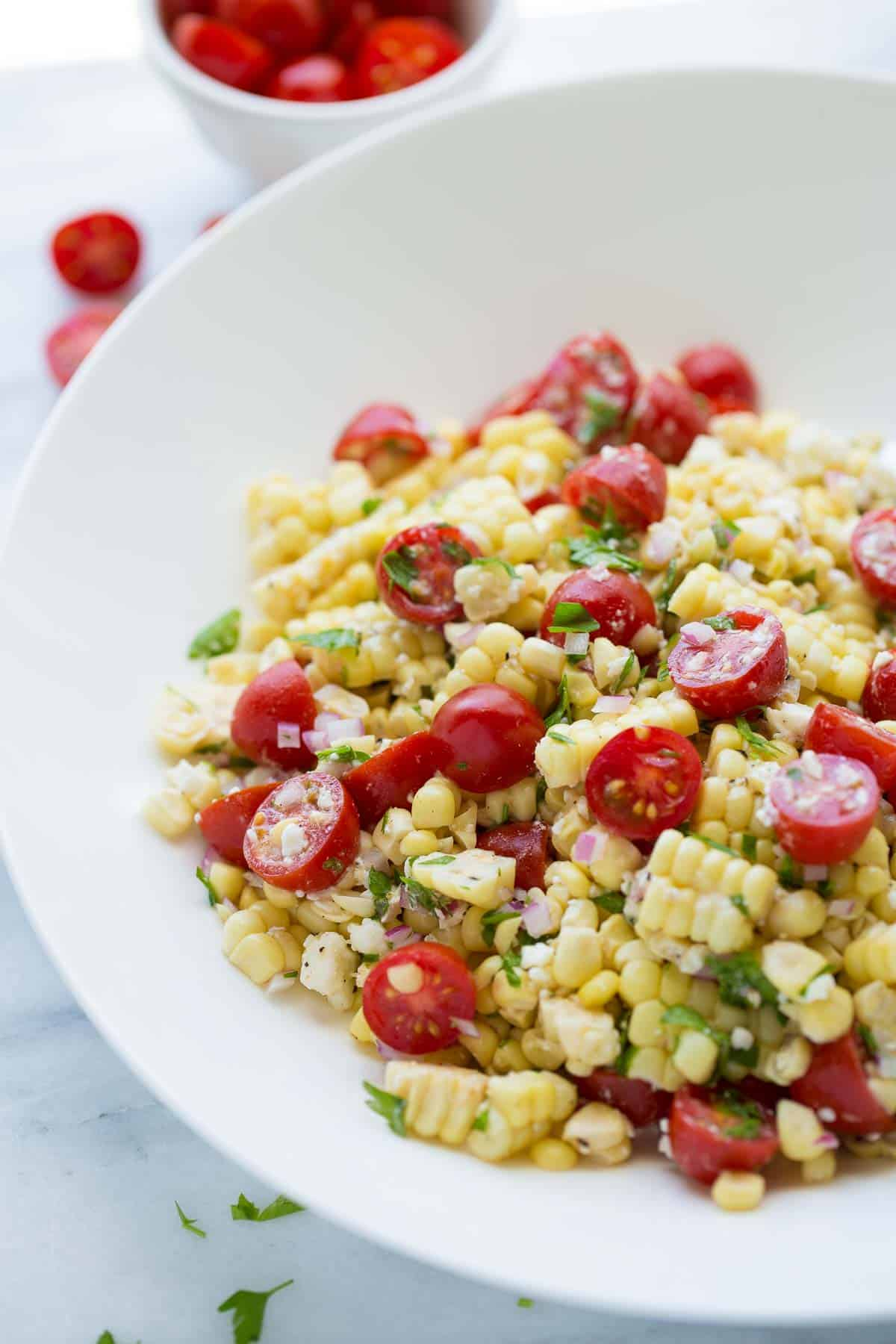 shot of corn salad in white bowl topped with parsley