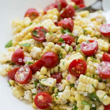 corn salad on white plate with serving spoon