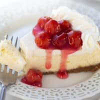 close up shot of cheesecake with cherries on white plate with fork
