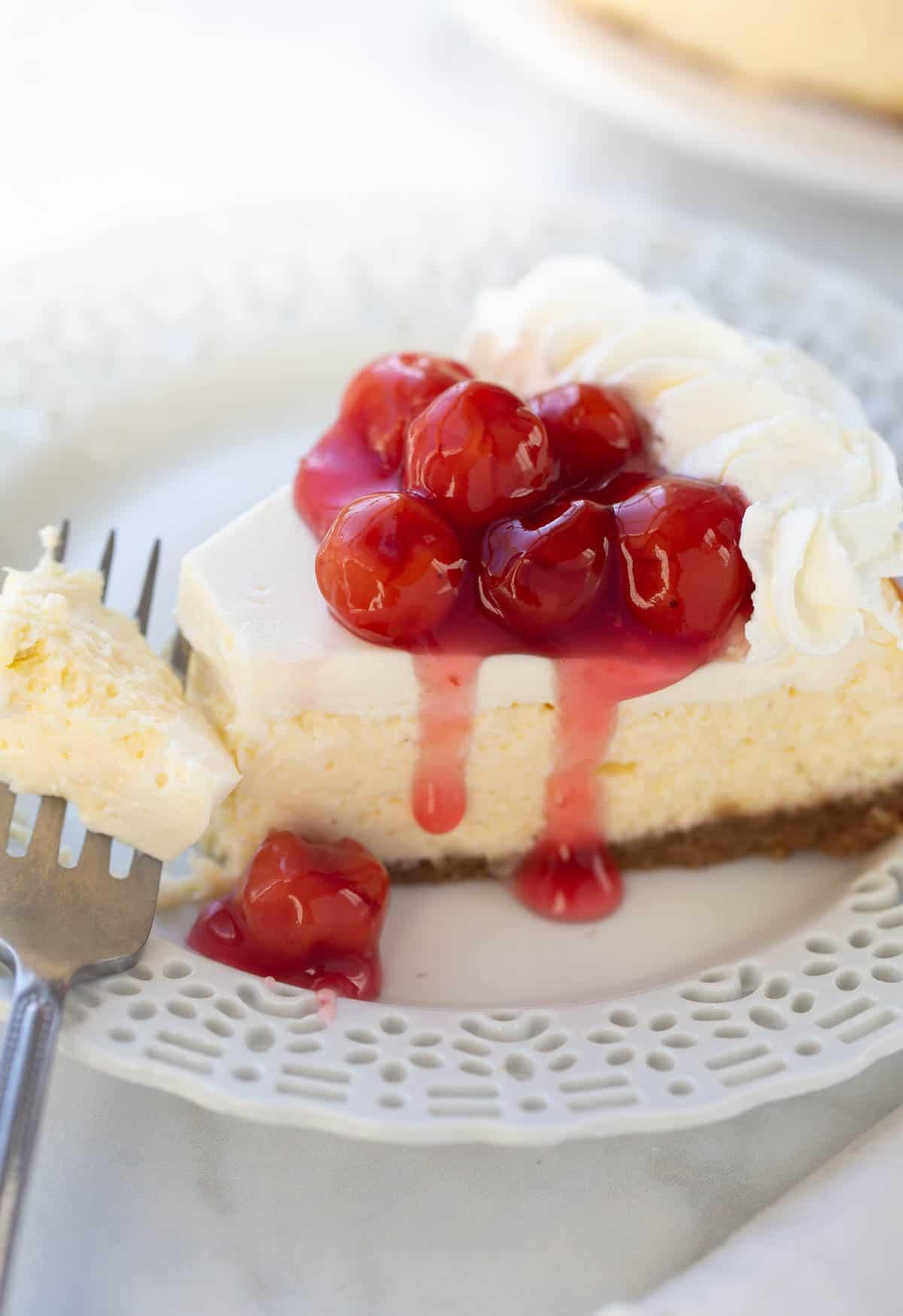 photo de gâteau au fromage sur assiette blanche garnie de cerises