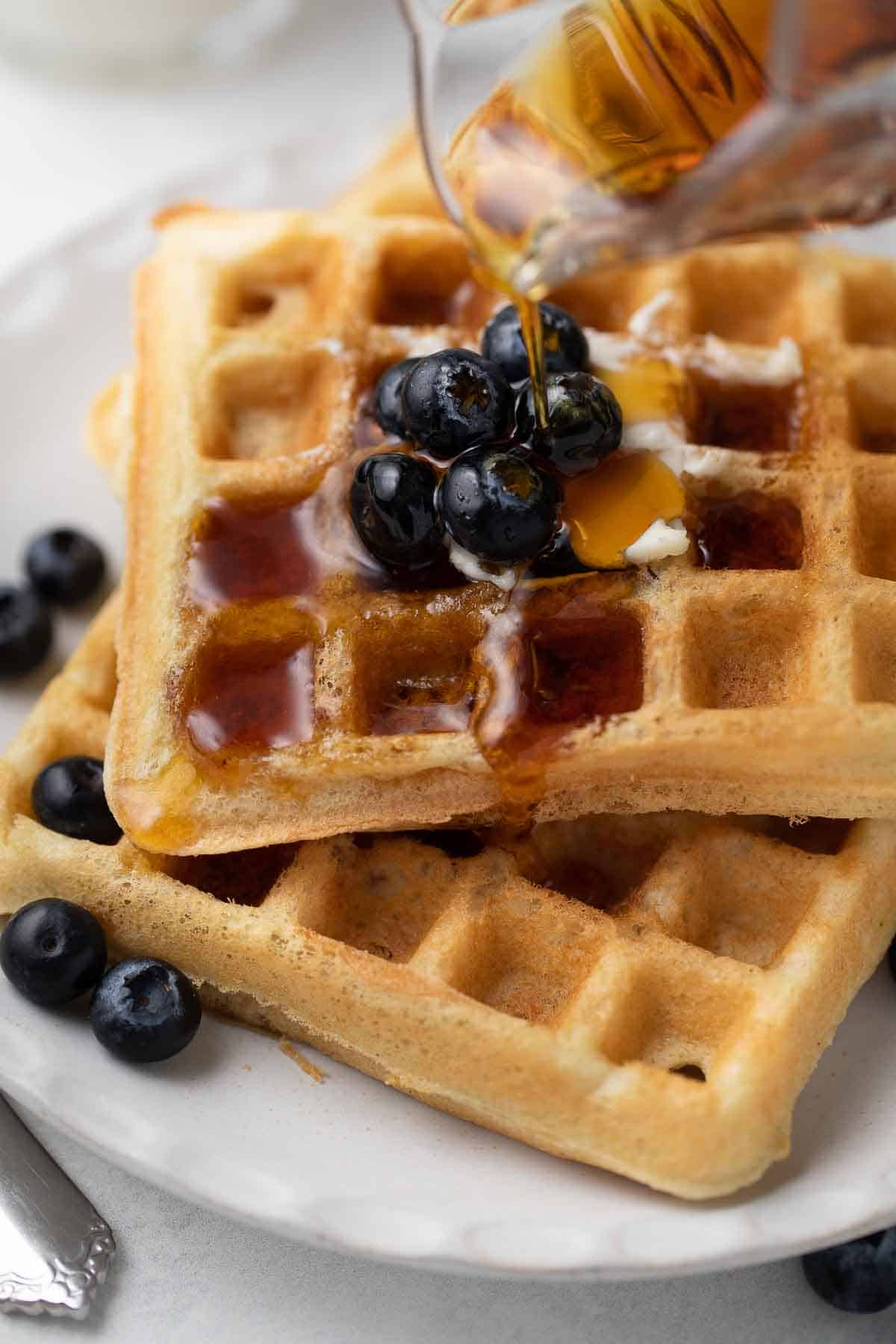 close up of gluten free waffles on a white plate topped with blueberries and maple syrup