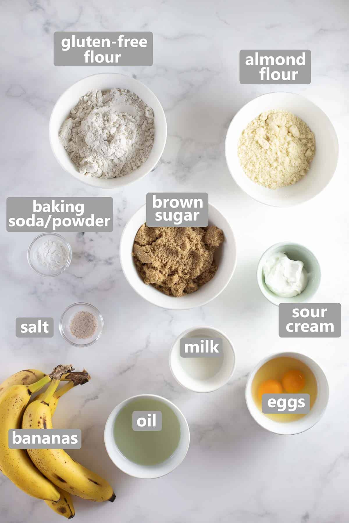 labeled bowls with ingredients for gluten-free banana muffins set out on marble background