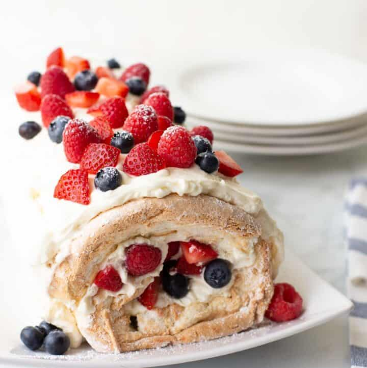 gluten-free angel food acke roll on white serving dish topped with berries