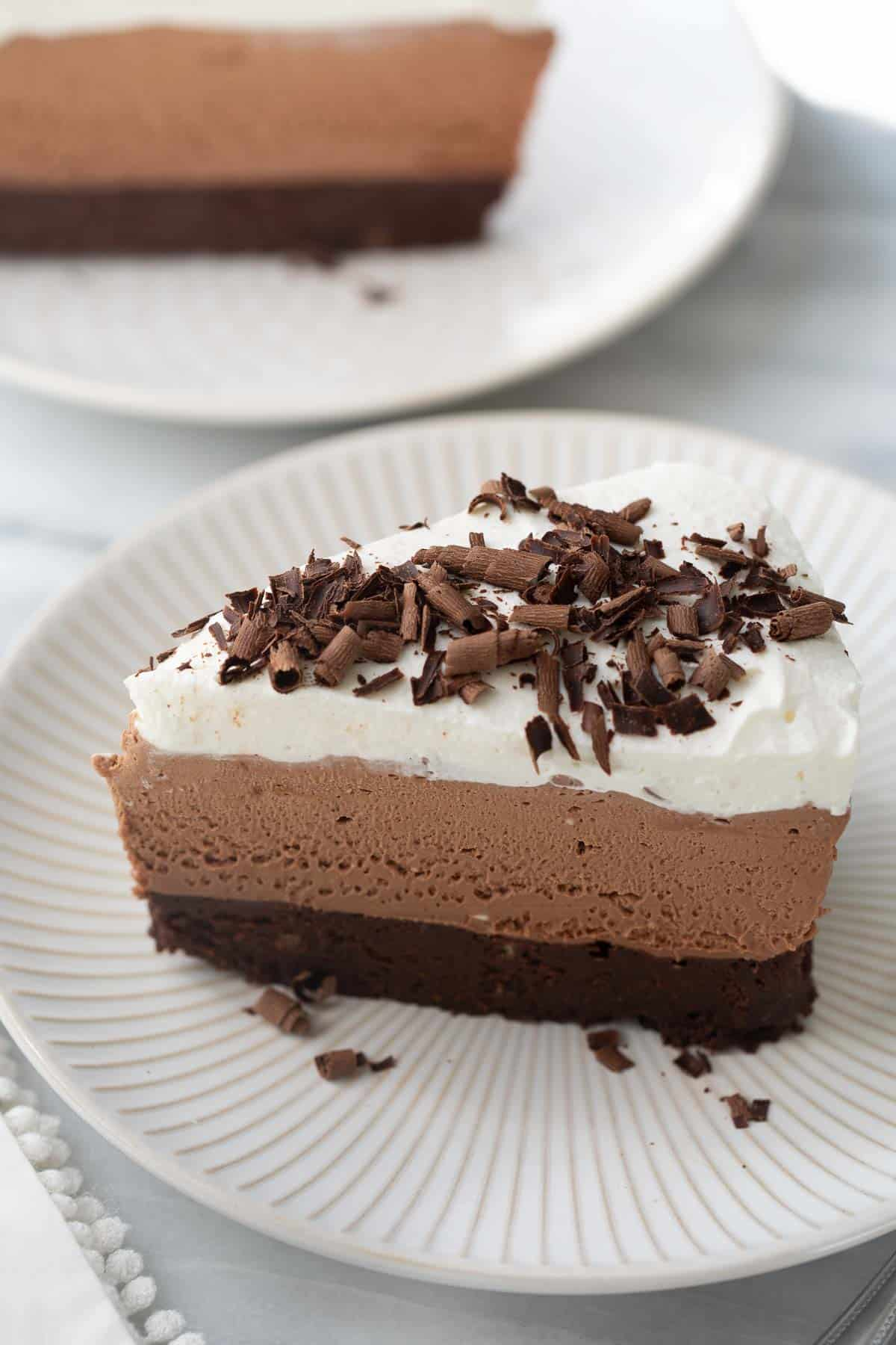 slice of chocolate mousse cake on white plate topped with chocolate shavings