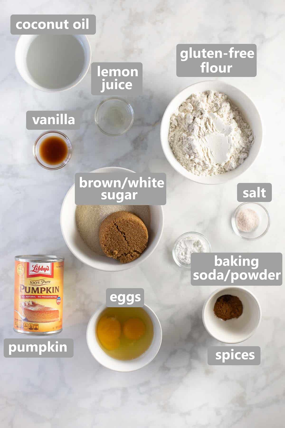 ingredients to make pumpkin muffins set out in bowls on marble background